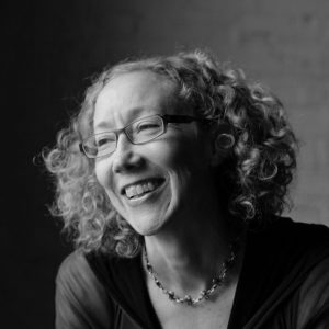 smiling woman with curly hair and glasses
