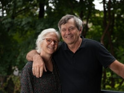 man with his arm around shoulder of woman with glasses