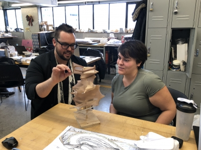 two people at a table building a wooden model